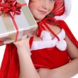 Girl dressed in a Santa costume holding aloft a present — Stockfoto