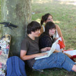 Teenagers sitting at the foot of a tree — Stock Photo