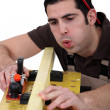 Tradesman blowing shavings off of a wooden plank - Stock Photo