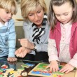 Woman and children with a wooden puzzle — Stock Photo