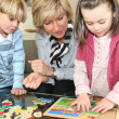 Woman and children with a wooden puzzle — Stock Photo #11073509