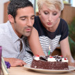 Stock Photo: Couple blowing birthday candle