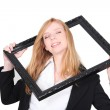 Pretty woman putting her head through a picture frame — Stock Photo