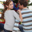A couple of teenagers sitting in front of the Christmas tree. — Stock Photo #11074737
