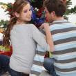 A couple of teenagers sitting in front of the Christmas tree. — Stock Photo