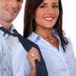 A businesswoman pulling her colleague by the tie. — Photo