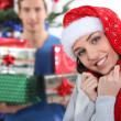 Couple sat by Christmas tree with presents — Stock Photo
