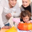 Little girl and parents carving pumpkin for Halloween — Stock Photo