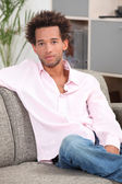 Young man sitting on a couch — Stock Photo