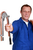 Plumber using tool to bend copper pipe — Stock Photo