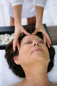 Woman being treated to head massage — Stock Photo