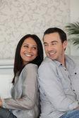 Happy couple sitting back to back — Stock Photo