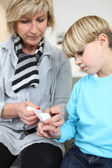 Grandmother healing her grandson's finger — Stock Photo