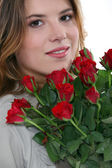 Young woman with a bunch of red roses — Stock Photo