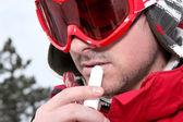 Male snowboarder using chap-stick — Stock Photo