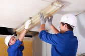Two electrician repairing office lighting — Foto Stock