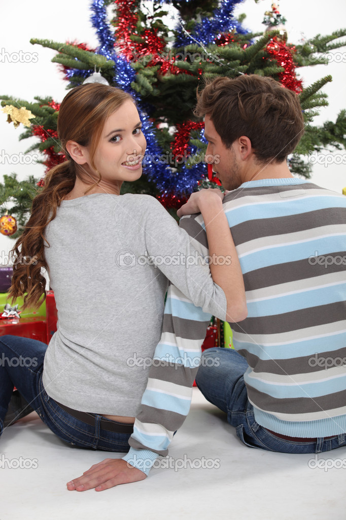 A couple of teenagers sitting in front of the Christmas tree.  Stock Photo #11074737