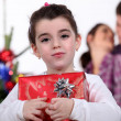 Young girl holding a gift on Christmas Day — Stock Photo