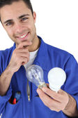 Young electrician smiling holding light bulbs — Stock Photo
