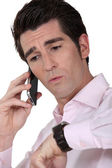 Man on the telephone checking watch — Stock Photo