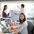 A woman at work with colleagues — Stock Photo #11307431