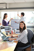 A woman at work with colleagues — Stock Photo