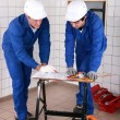 Two skilled tradesman in blue jumpsuites watching a drawing - Stock Photo