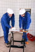 Two skilled tradesman in blue jumpsuites watching a drawing — Stok fotoğraf