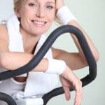 Woman on exercise bike — Stok fotoğraf #11390559