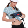Sexy woman holding an electric screwdriver — Stock Photo