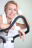 Woman on exercise bike — Stock Photo