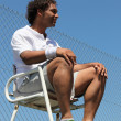 Portrait of man dressed in sportswear sat in tennis umpire's chair — Stock Photo