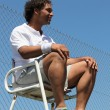 Portrait of man dressed in sportswear sat in tennis umpire&amp;#039;s chair - Stock Photo