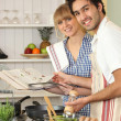 Couple preparing a meal with the help of a cookbook — Stock Photo #11465347