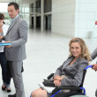 Businesswoman in a wheelchair with colleagues checking in at reception — Stock Photo #11465481
