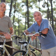Senior men having a bike ride in the woods — Stock Photo