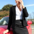 Woman making a business call by her car — 图库照片