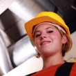 Stock Photo: Young female worker by exposed ventilation