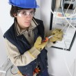 Young electrician stood by fuse box — Stock Photo