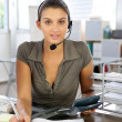 Brunette administrator wearing telephone head-set — Stock Photo