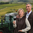 Farming couple stood in field in front of tractor — Stock Photo