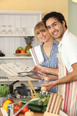 Couple preparing a meal with the help of a cookbook — Stock Photo