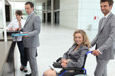 Businesswoman in a wheelchair with colleagues checking in at reception — Stock Photo