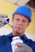 Tradesman holding a jar of glue — Stock Photo