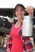 Female farmer milking the cows — Stock Photo