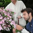 Young man gardening with older woman — Stock Photo #11485361