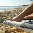Womrelaxing on sun lounger at beach — Stock Photo #11485387