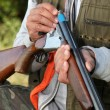 Stock Photo: Hunter loading shotgun
