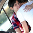 Stock Photo: Embracing couple in a car