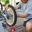 Man repairing a bike on his terrace - Stock Photo